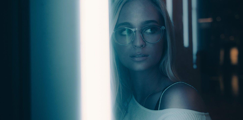 Frau in blau-grünem Licht mit Brille