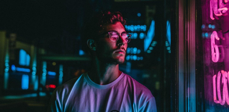 """Mann in dunkler Umgebung mit Brille in der sich """"NEED"""" in neonpink spiegelt"""