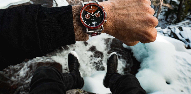 Mann mit Armbanduhr in den Bergen