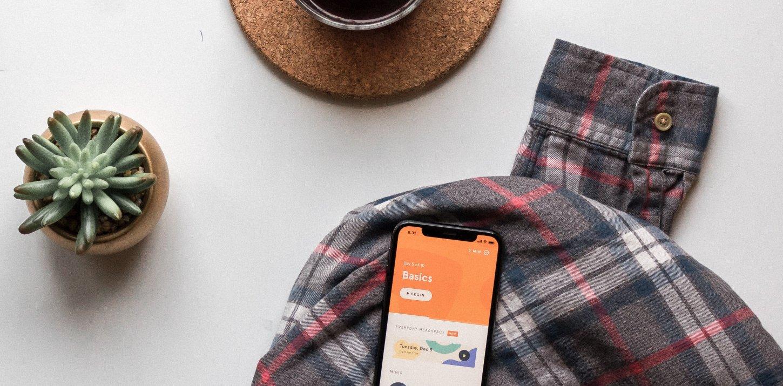 Hemd, Kaffee, Pflanze als geringe Ablenkung neben dem Handy für Achtsamkeit